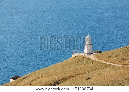 white lighthouse on the background of the sea in summer