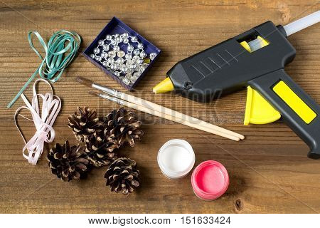 Making Christmas decorations from pine cones. Children project step by step photo instructions. Step 1. Preparation of materials and tools (gouache brushes ribbons beads glue gun)
