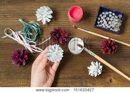 Making Christmas decorations from pine cones. Children project step by step photo instructions. Step 3. Child painted pine cones in white and burgundy color