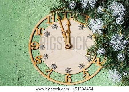 Decorative clock showing midnight and the arrival of the New Year decorated Christmas tree branch on a green background