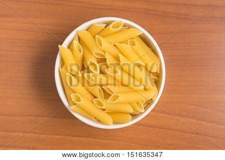 Penne into a bowl over a wooden table
