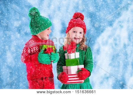 Little girl and boy in red and green knitted hat holding Christmas present boxes in winter park on Xmas eve. Kids play outdoor in snowy winter forest. Children opening presents. Panorama size.
