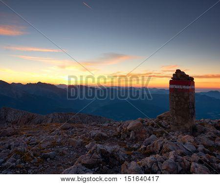 Border Stone On Apine Gravel  Cliff. Austria Germany Border. Daybreak Horizon