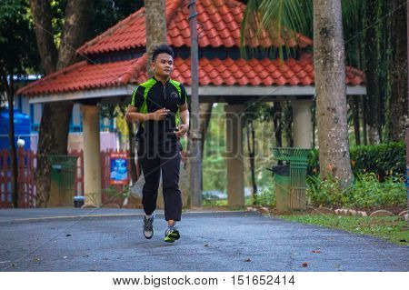 Labuan,Malaysia-Oct 13,2016:Athletic young man running in Labuan Botanical Park,Labuan,Malaysia. Active lifestyle enthusiasts concept