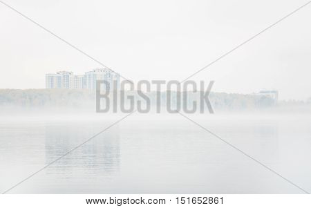Heavy fog on the lake Senezh in Solnechnogorsk fall in calm weather. View of the residential high-rise buildings through the haze. Autumn morning water landscape