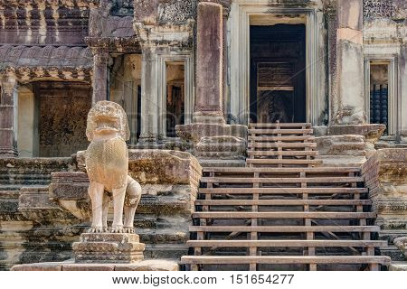 Ancient ruins of temple complex Angkor Wat surrounded by palm trees Siem Reap Cambodia. Lions guarding the entrance to the ruins