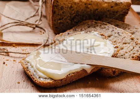 Still life fresh whole wheat bread with butter and honey rustic wooden table background