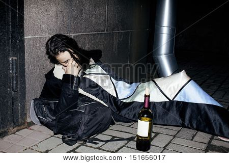 young poor ttenage girl sitting at dirty wall on floor with bottle of vine, poor refugee alcoholic, hopeless homeless woman in depression, real junky concept close up