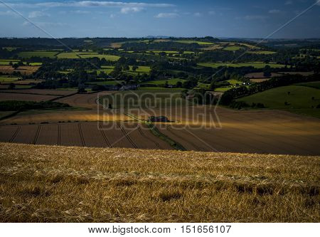 Sun illuminates patches of bare ploughed earth and a barn deep in a valley in Dorset