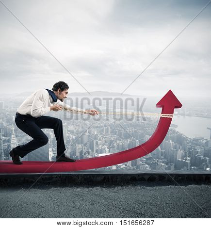 Determinated businessman with much effort lifts statistics arrow with a rope in a skyscraper roof