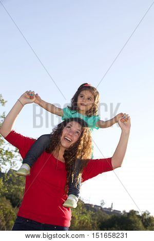 Teenager with Little Girl Blowing Bubbles Outside in a Field.  They both have long dark curly hair.