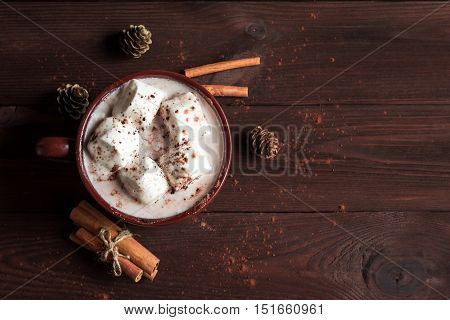 Christmas drink. Hot chocolate in a mug marshmallows cinnamon sticks and fir cones top view flat lay