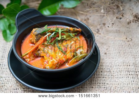 Chuchi mackerel curry-fried fishstyle Thai food on a table covered with a cloth sack.