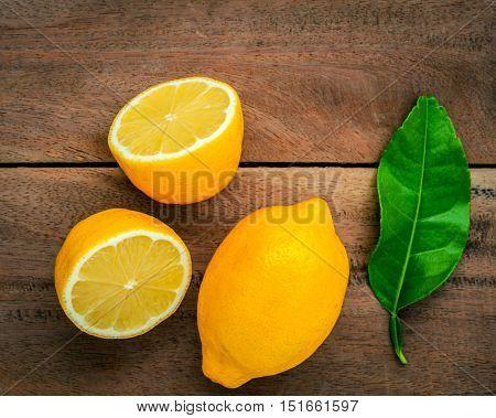 Fresh Lemons And  Lemons Leaves On Rustic Wooden Background. Fresh Lemons And Lemon Slice On Wooden