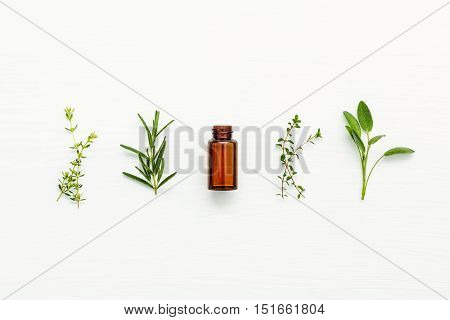 Bottle Of Essential Oil With  Fresh Herbal Sage, Rosemary, Lemon Thyme And Thyme  Setup With Flat La