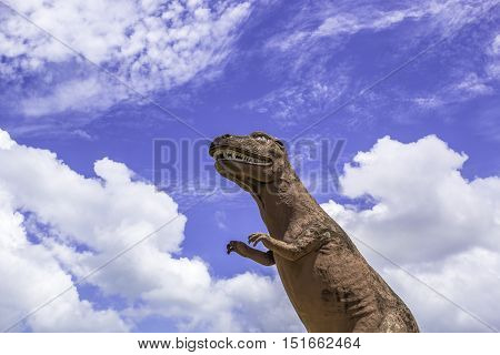 Dinosaur statue standing with blue sky background
