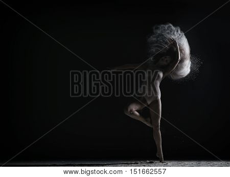 Strange dance with dust performed by graceful female dancer
