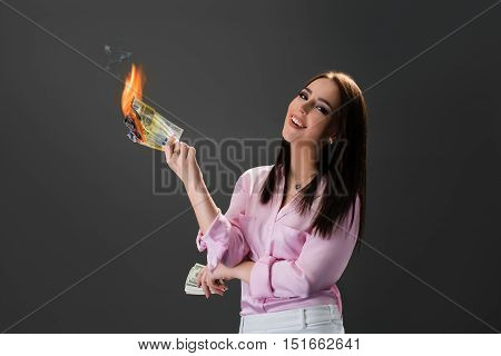 Smiling young woman burns money. Concept of extravagance