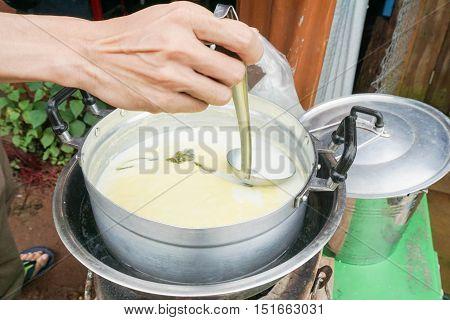 man use dipper to ladle fresh milk from aluminium pot