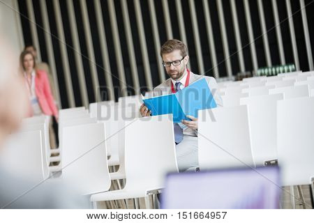 Businessman reading file while sitting in seminar hall at convention center