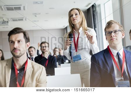 Confident businesswoman gesturing while holding microphone during seminar