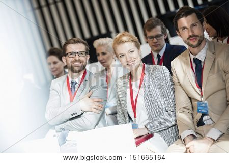 Portrait of happy business people sitting in seminar hall