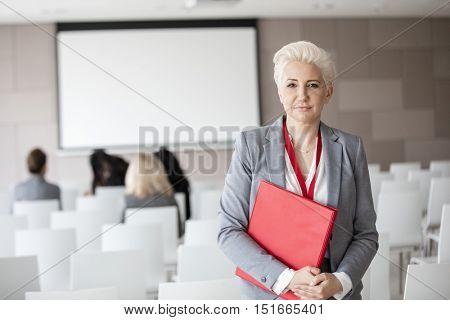 Portrait of confident businesswoman holding file in seminar hall