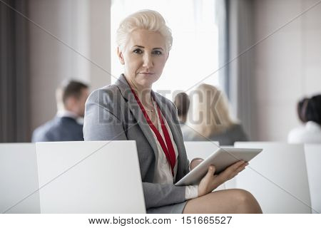 Portrait of confident businesswoman holding digital tablet while sitting in seminar hall