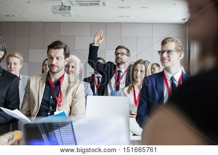 Businessman raising hand during seminar