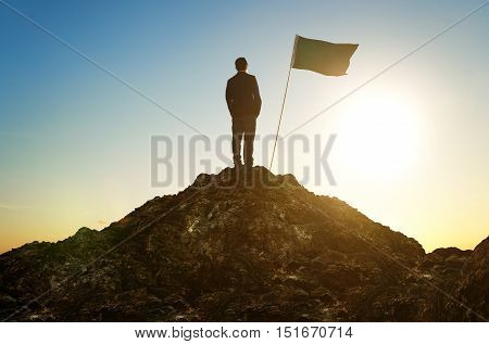 business success leadership achievement and people concept - silhouette of businessman with flag on mountain top over sky and sun light background