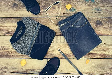 Women's clothing and accessories: grey sweater, jeans, belt, sneakers, sunglasses, yellow leaves on wooden background. Top view. Toned image.