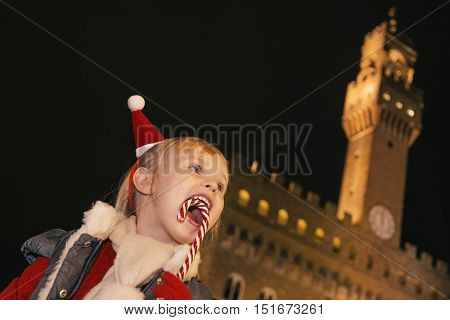 Smiling Girl In Front Of Palazzo Vecchio Eating Christmas Cane
