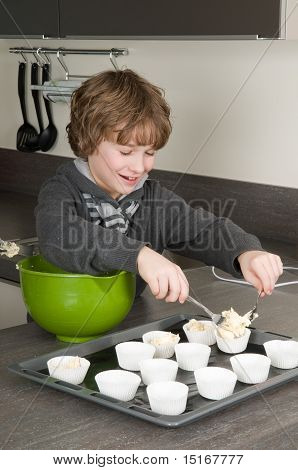 Kid Filling Cakecups With Dough