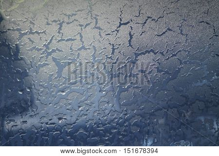 lace ornament on window of car ice in shape of drops, cracks fragile texture of white crystals