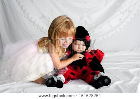 A preschool aged girl hugs her younger sibling who is dressed in a ladybug costume. The older sister has a look of bliss on her face and the younger looks a bit sad and annoyed. The little girl is wearing orthopedic shoes.