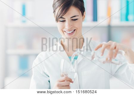 Doctor Holding A Glass Of Water And A Bottle