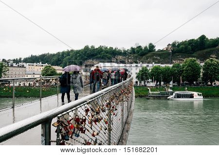Salzburg Austria - April 30 2015: Salzach river and bridge a rainy day. Salzburg is renowned for its baroque architecture and was the birthplace of Mozart. It is an Unesco World Heritage Site.