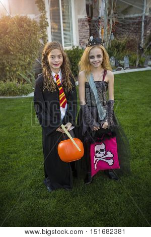 Little kids going trick or treating on Halloween in their costumes in a fun neighborhood