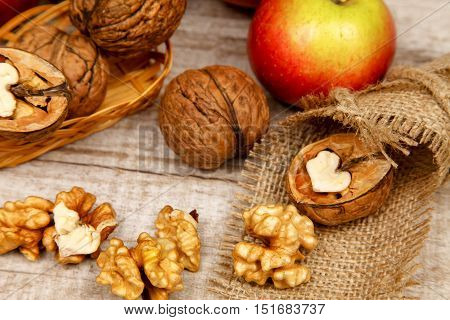 Whole walnuts and kernels on a table with fresh red apples