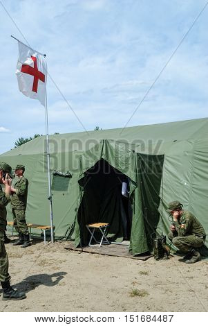 Tyumen, Russia - June 11, 2016: Race of Heroes project on the ground of the highest military and engineering school. Cadet holds a radio station and communicates near medical tent