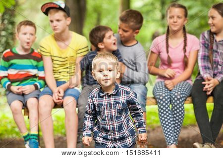 Close-up portrait of cute little boy in the foreground and a group of children on a bench behind him