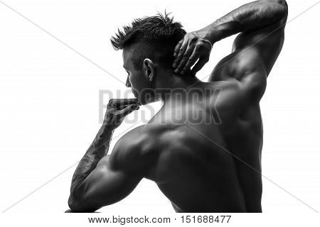 The beautiful and strong young guy.  Black and white photo, silhouette. Hidden in the shadow.  Male silhouette. view from the back.