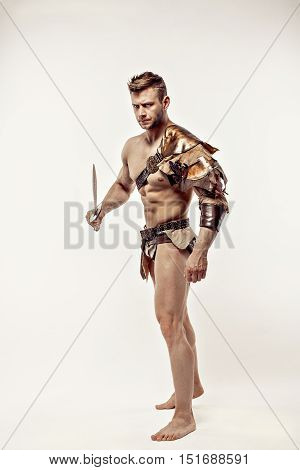 Portrait of handsome strong gladiator in leather costume holding sword and looking away.Studio shot, isolated.