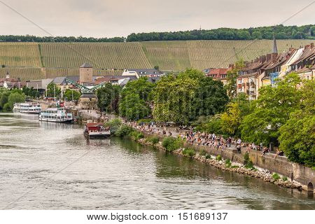Wurzburg Germany - May 22 2016: People sitting at the bank of the Main River in the evening in Wurzburg Lower Franconia Bavaria Germany. Vineyards in the background.