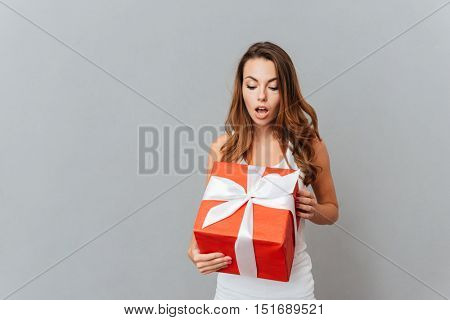 Cute surprised young woman open present box isolated on a gray background