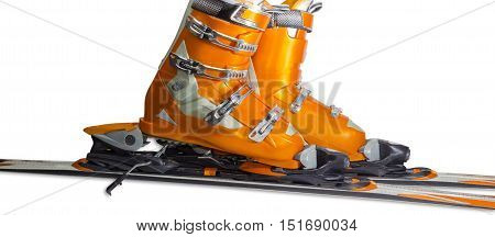Orange alpine ski boots with four buckles in ski binding. One shoe is completely fastened to the ski a second just put in binding.