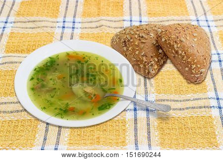 Homemade chicken soup in white dish with a spoon and two multi-grain triangular shaped breads sprinkled with whole different seeds on checkered tablecloth