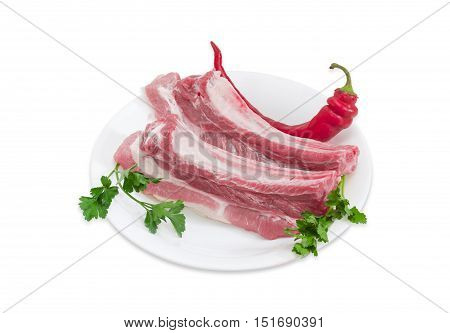 Two pieces of uncooked pork belly with ribs chili pepper and twigs of parsley and cilantro on a dish on a light background