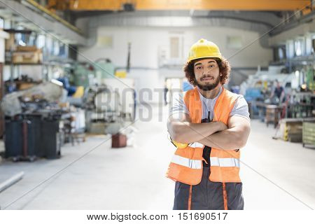 Portrait of young manual worker standing arms crossed in factory