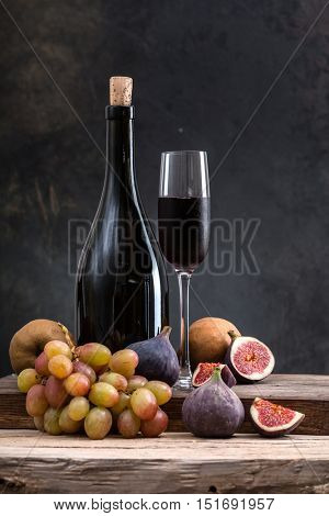 bottle of wine with fruit on a wooden board